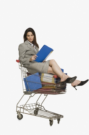 consumerism: Businesswoman sitting in a shopping cart with files LANG_EVOIMAGES