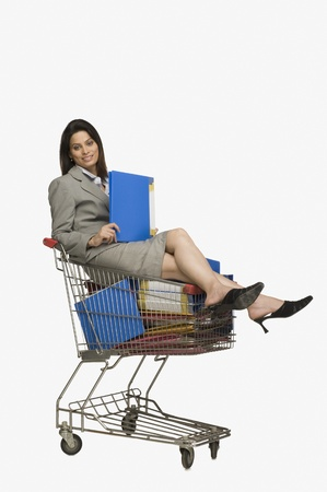 Businesswoman sitting in a shopping cart with files Stock Photo - 10124606