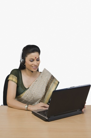 Female customer service representative working on a laptop Stock Photo - 10124986
