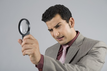 find: Businessman looking through a magnifying glass
