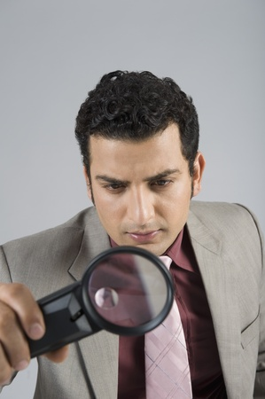 Businessman looking through a magnifying glass Stock Photo - 10169204