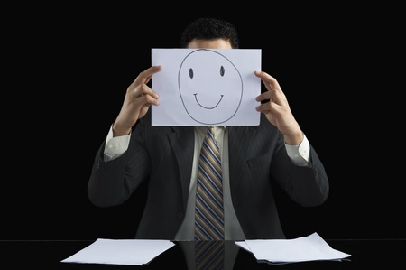 Businessman holding a smiley face paper in front of his face Stock Photo - 10125730