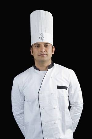 chefs whites: Portrait of a chef standing with hands behind back