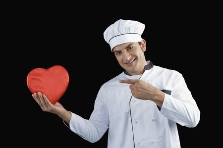 Chef pointing towards a heart shape gift Stock Photo - 10124267