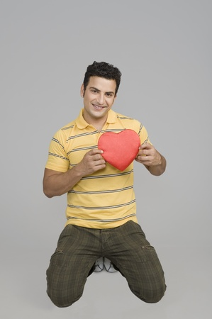 Man proposing with a heart shape gift 写真素材