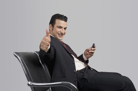 Zakenman die een mobiele telefoon en zien thumbs up teken