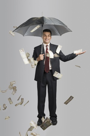 Money raining over a businessman Standard-Bild