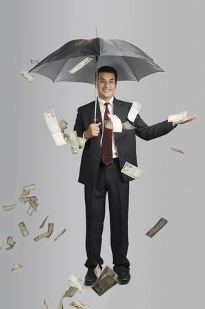Money raining over a businessman Stok Fotoğraf