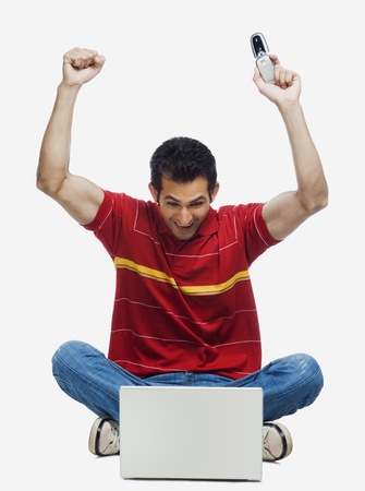 cheer full: Man cheering in front of a laptop and holding a mobile phone
