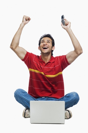 Man cheering in front of a laptop and holding a mobile phone Stock Photo - 10124490