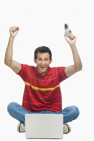 Man cheering in front of a laptop and holding a mobile phone Stock Photo - 10125401