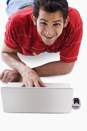 Portrait of a man using a laptop and smiling Stock Photo - 10169159