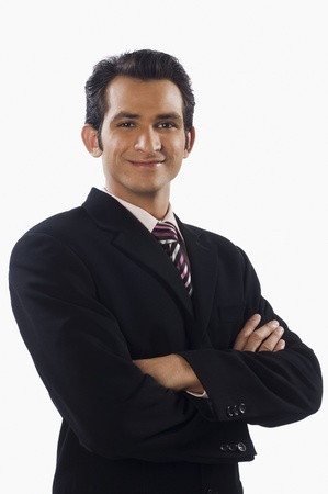 Portrait of a businessman standing with his arms crossed and smiling Stock Photo - 10125573