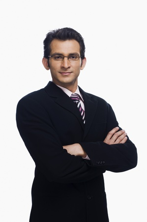 businessman standing: Portrait of a businessman standing with his arms crossed
