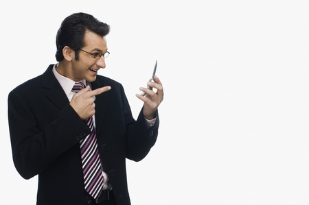 clipping  messaging: Businessman pointing at a mobile phone and smiling LANG_EVOIMAGES