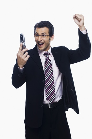 Businessman clenching fist while reading a text message on a mobile phone Stock Photo - 10125672