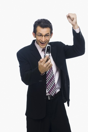 clipping  messaging: Businessman clenching fist while reading a text message on a mobile phone