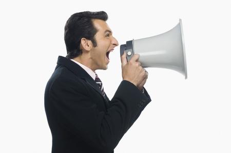 loudspeaker: Businessman shouting into a megaphone