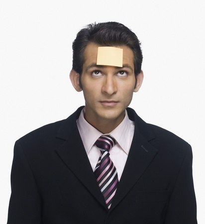 Businessman looking at a sticky note on his forehead Stock Photo - 10124427