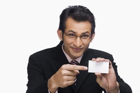 Portrait of a businessman showing a business card Imagens