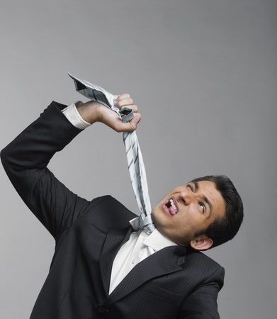 strangling: Close-up of a businessman strangling himself with necktie