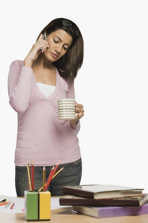 Female fashion designer drinking coffee and talking on a mobile phone Stock Photo - 10124332