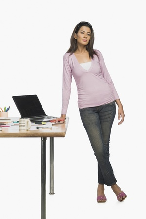 creativity: Female fashion designer standing in her office LANG_EVOIMAGES