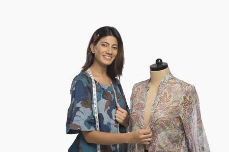 designer: Female fashion designer trying a dress on a mannequin and smiling LANG_EVOIMAGES