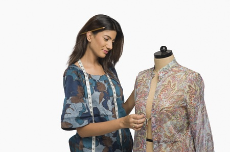 Female fashion designer trying a dress on a mannequin