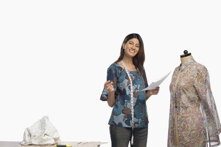designer: Female fashion designer sketching a dress
