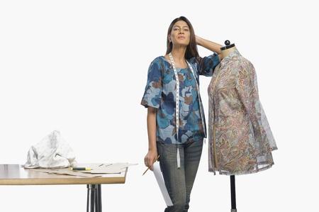 designer: Female fashion designer leaning on a mannequin