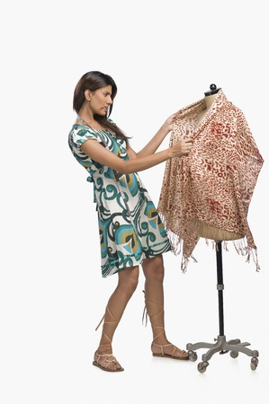 Female fashion designer trying a dress on a mannequin Stock Photo - 10124636