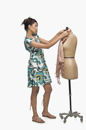 designer: Female fashion designer trying a dress on a mannequin