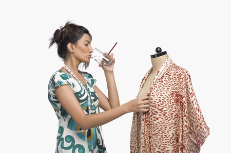 designer: Female fashion designer trying a dress on a mannequin and drinking water LANG_EVOIMAGES