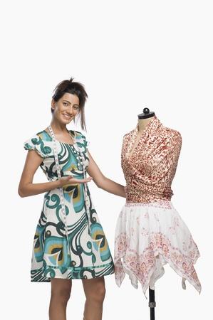 designer: Female fashion designer showing a dress LANG_EVOIMAGES