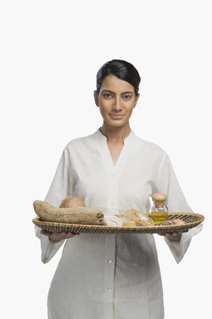Woman holding a tray of products for aromatherapy