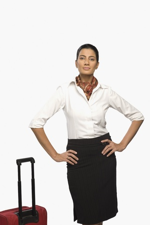 high flier: Portrait of an air hostess with her luggage