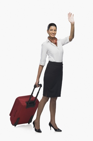 Air hostess carrying her luggage and waving Stock Photo - 10123871