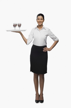 hostess: Air hostess carrying a tray of wine glasses