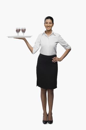 hotesse de l air: Hôtesse aérienne transportant un plateau des verres à vin