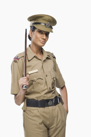 Portrait of a female police officer holding a stick 版權商用圖片