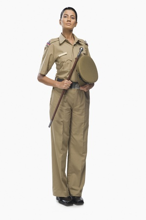 Portrait of a female police officer holding a stick 免版税图像