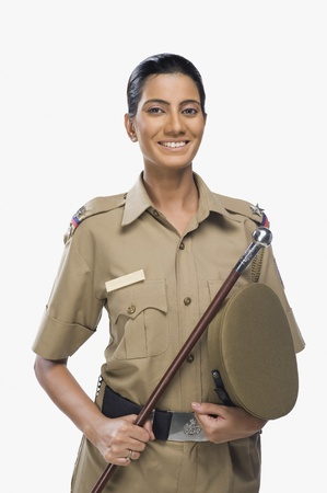 Portrait of a female police officer holding a stick and smiling Stock Photo - 10169439