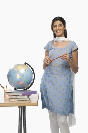 kameez: Female teacher holding a pen and smiling