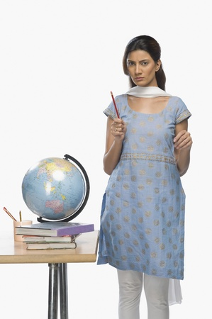 kameez: Female teacher standing beside a desk
