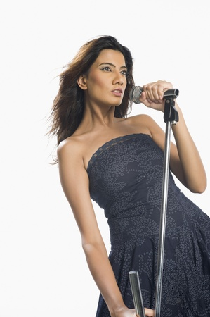 off the shoulder: Woman singing into a microphone LANG_EVOIMAGES