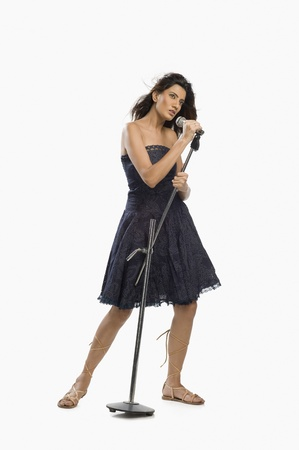 off shoulder: Woman singing into a microphone LANG_EVOIMAGES