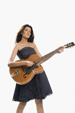 off shoulder: Woman playing a guitar