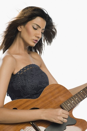 off the shoulder: Close-up of a woman playing a guitar LANG_EVOIMAGES
