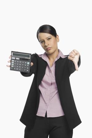 電卓を持ち、親指を下に見せるビジネスウーマン